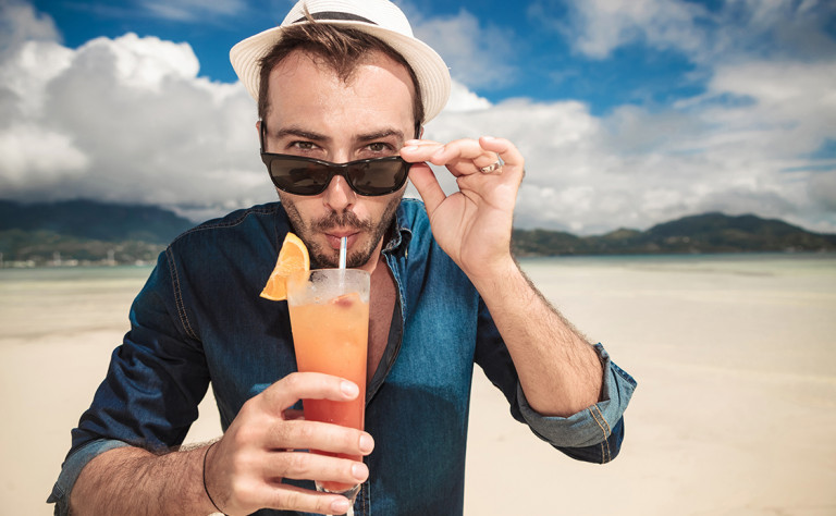 Guy drinking cocktail on beach